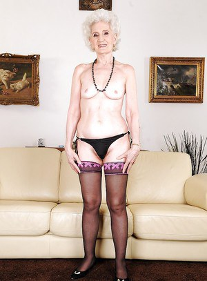 Granny takes off her panties to show her hairy pussy in stockings