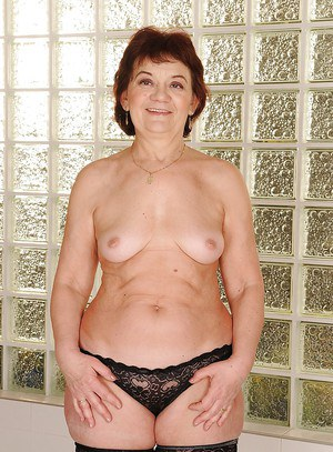 Slutty granny in stockings strips to her naked body and hairy pussy