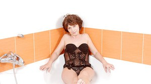 Mature lady in lingerie gets in the bath to play with her sex toys