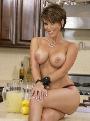 Big titted MILF strips in the kitchen and feels her craving pussy