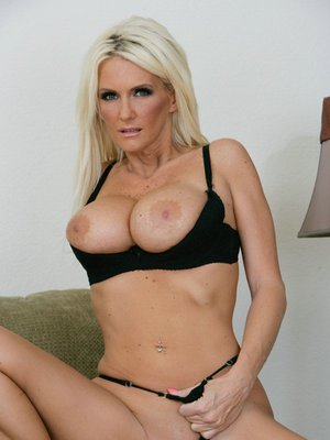 Mature yet sexy babe is stripping and spreading her pussy