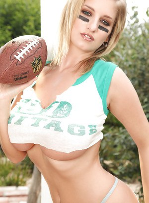 Sports babe with huge melons is posing outdoor playing football