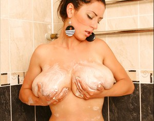 Big titted babe gets undressed in the bath to show off her boobs