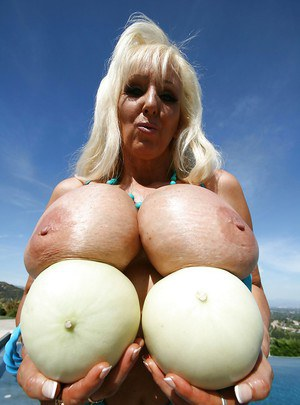 Mature babe Tia Gunn fondles her tits outdoor by the pool