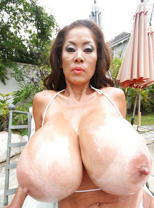 Mature Asian babe Minka boasting of her big melons outdoor
