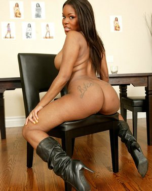 Busty ebony babe Candice Nicole strips her dress to pose in boots