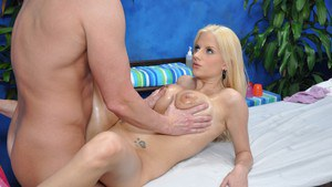 Busty blonde gets her juggs oiled up and fucked on the massage table