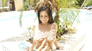 Busty MILF Ava Addams stripping and posing seductively in the pool