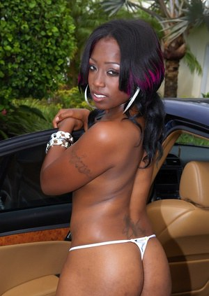 Sexy black girl strips off red dress and poses in tiny white panties