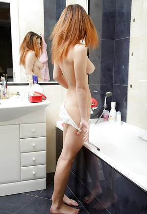 Petite redhead babe Maggie C posing and teasing her slit in the bath