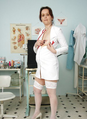 Horny mature nurse in uniform and white stockings playing with her toys