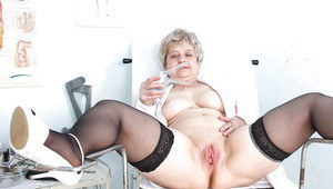 Busty aged nurse in uniform and black stockings spreading her legs