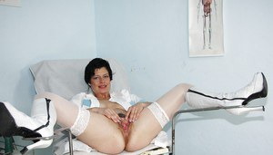 Seductive mature nurse in white stockings playing with a huge dildo