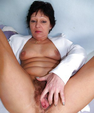Filthy mature nurse in uniform teasing her hairy twat with a gyno tool