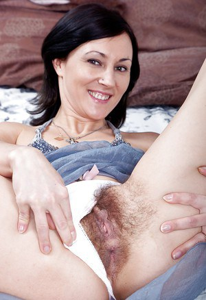 Seductive MILF with shaggy cunt Kristy taking off her clothes