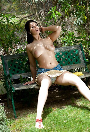 Gorgeous brunette babe with petite melons Kandie Luv stripping outdoor