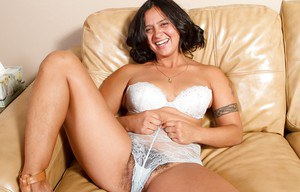Chubby brunette MILF with hairy armpits Gigi stripping and posing
