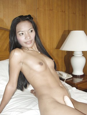 Fuckable asian babe stripping and playing with a dildo on the bed