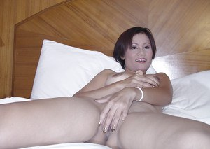 Stunning asian babe stripping and playing with a toy on the bed