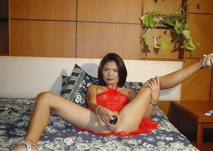 Horny asian babe in red dress masturbating her cunt with a dildo