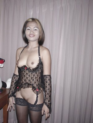 Fuckable asian babe in erotic lingerie and stockings posing on the bed