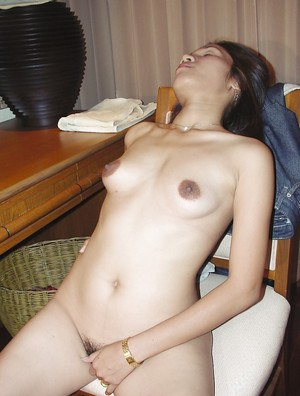 Horny asian babe slipping off her clothes and masturbating her hairy pussy