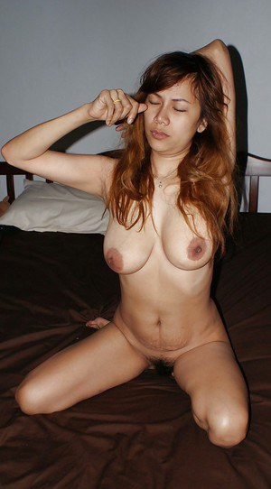 Cute asian babe with big tits taking off her panties and posing on the bed