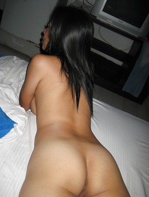 Seductive asian babe with big tits stripping and posing naked on the bed