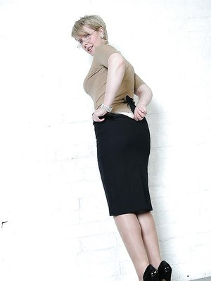 Short haired mature lady in glasses slipping off her skirt