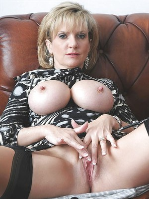 Lusty mature lady in stockings spreading her legs and teasing her pussy