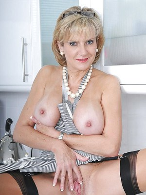 Gorgeous mature babe showing off her sexy curves in the kitchen
