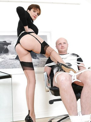 Voluptuous femdom babe in stockings gives a tugjob to a bound guy