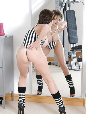 Mature lady in sport outfit exposing her sexy curves in front of the mirror