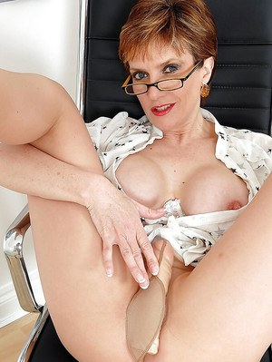 Busty mature lady in glasses posing with a dildo under her pantyhose