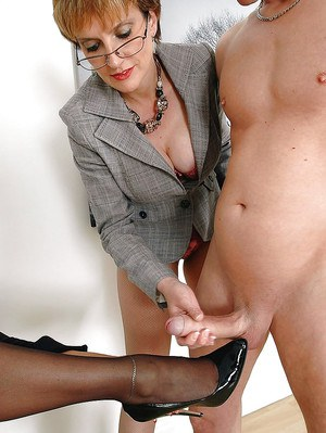 Kinky mature lady in glasses jerking off a dick on her friend's foot