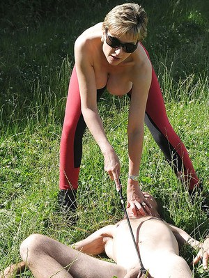 Gorgeous matur femdom in sunglasses whipping her manslave outdoor