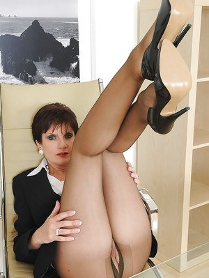 Gorgeous mature lady in ripped pantyhose exposing her pussy