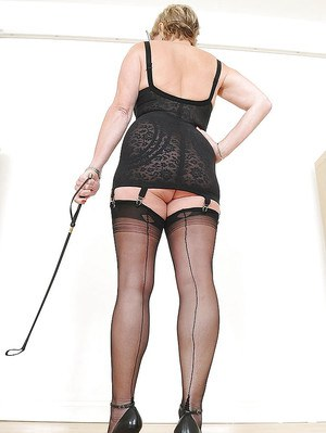 Fatty mature lady with ample ass posing in black nylon stockings