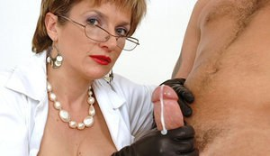 Lusty mature femdom in glasses jerks a cock untill it explodes with cum