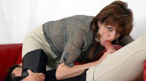 Lusty mature lady in black boots gives a blowjob to a younger guy