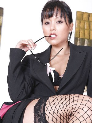 Seductive asian babe in fishnet stockings taking off her skirt