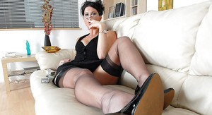 Fully clothed fetish MILF in glasses posing on the sofa and smoking