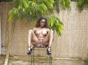 Fuckable ebony babe on high heels stripping off her clothes outdoor