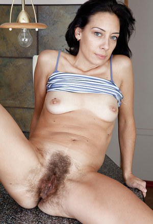 Seductive mature lady stripping and exposing her bushy twat