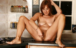Fuckable mature lady stripping and showing off her hairy twat