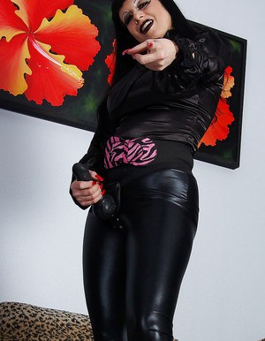 Seductive mature fetish babe posing with strapon over her latex leggings