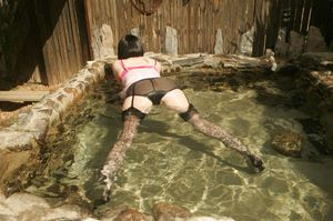 Fully clothed mature lady in nylon stockings posing in the pool