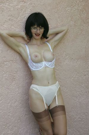 Sexy mature lady in glasses having fun and stripping outdoor