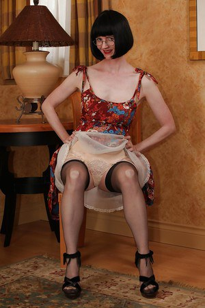 Seductive mature lady in fancy dress doing upskirt and stripping