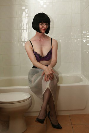 Seductive mature lady in glasses getting her lingerie wet in the bath